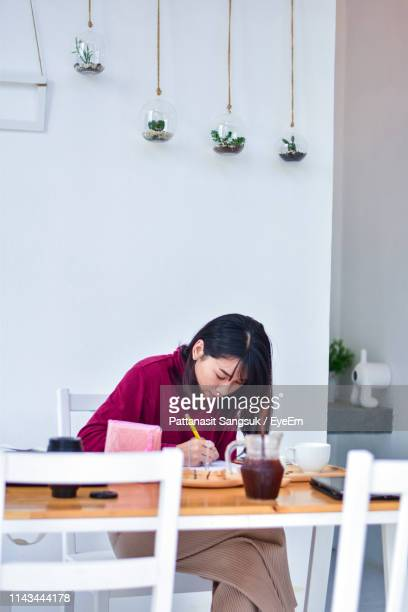 woman writing on book at table - pattanasit stock pictures, royalty-free photos & images