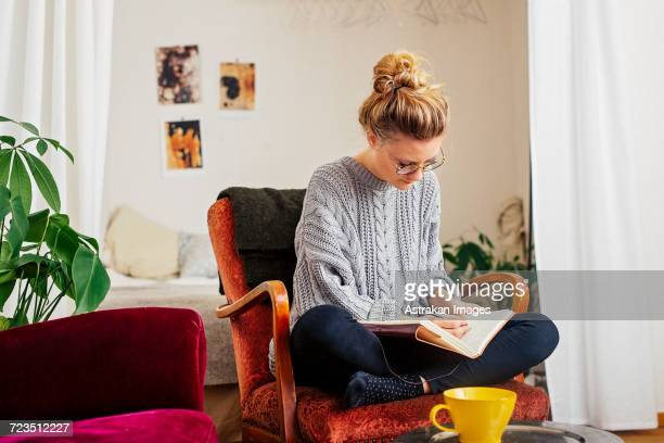 woman writing on book while sitting on chair at home - sweater stock photos and pictures