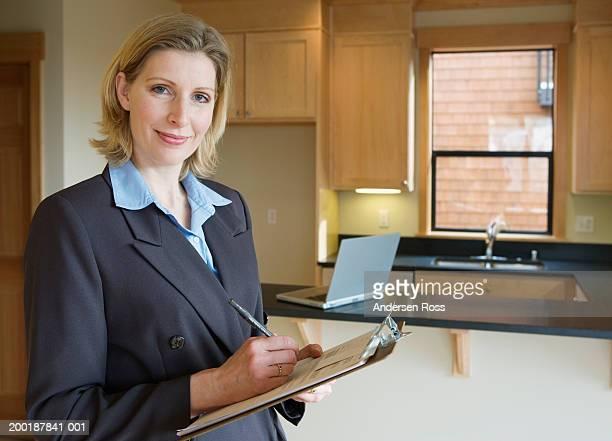 Woman writing on clipboard in empty domestic kitchen, portrait