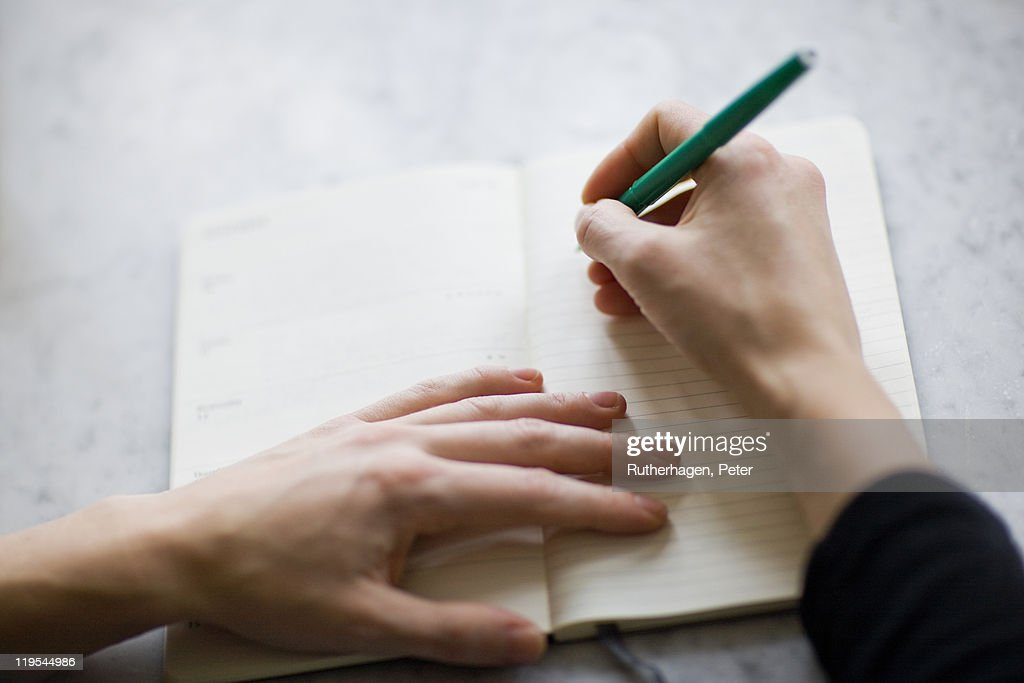 Woman writing on diary : Stockfoto