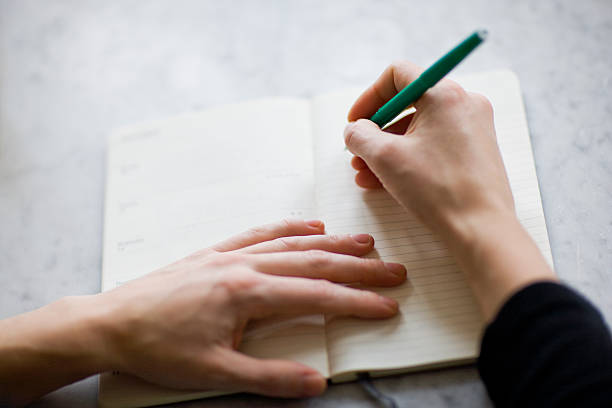 woman writing on diary - write down stock pictures, royalty-free photos & images