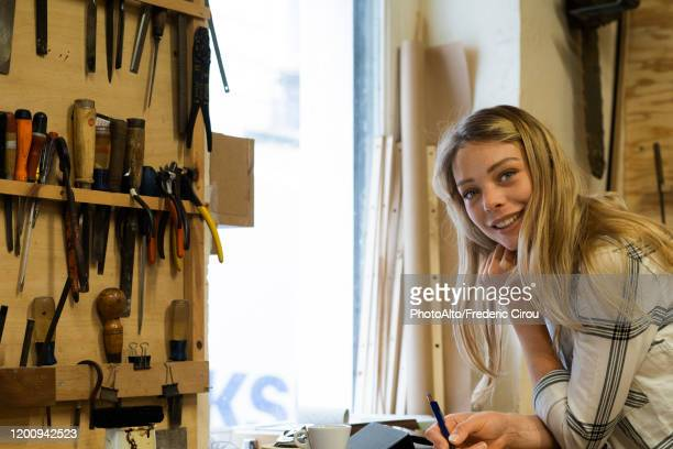 woman writing on notepad in workshop - three quarter length stock pictures, royalty-free photos & images