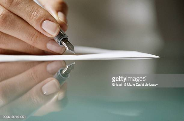 Woman writing on paper, reflected in glass table, close-up