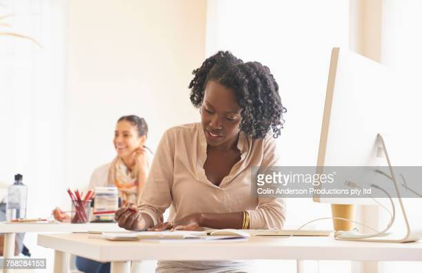 Woman writing on paperwork in office