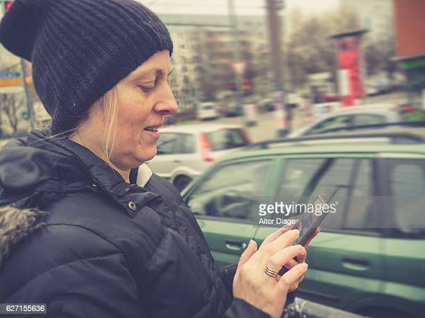 Woman writing on smart phone at the street while looking at it.