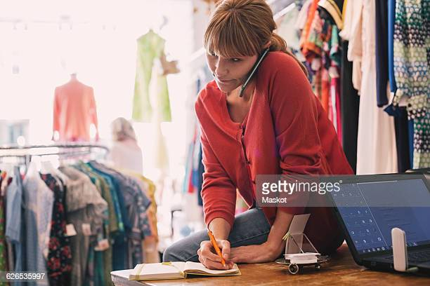 Woman writing order in diary while talking on smart phone at thrift store