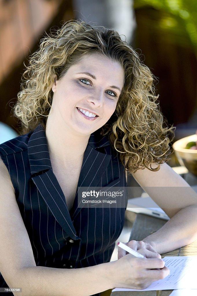 Woman writing outdoors : Stockfoto