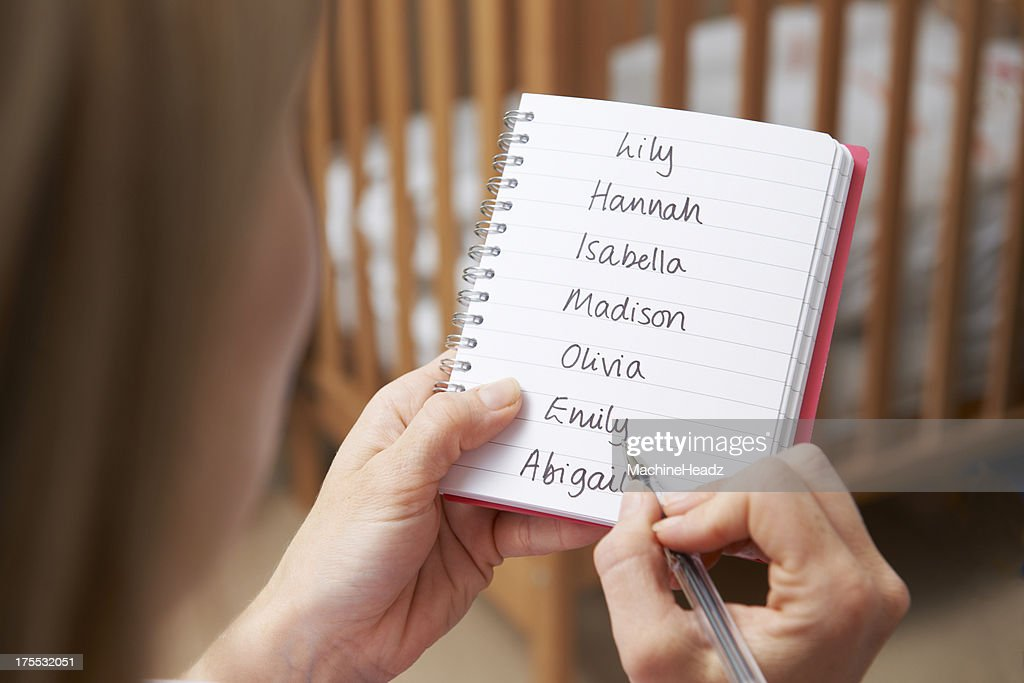 Woman Writing Possible Names For Baby Girl In Nursery : Stock Photo