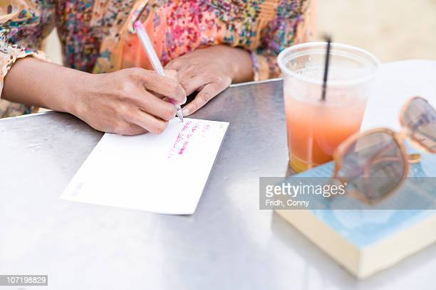 Woman writing postcard at outdoor table