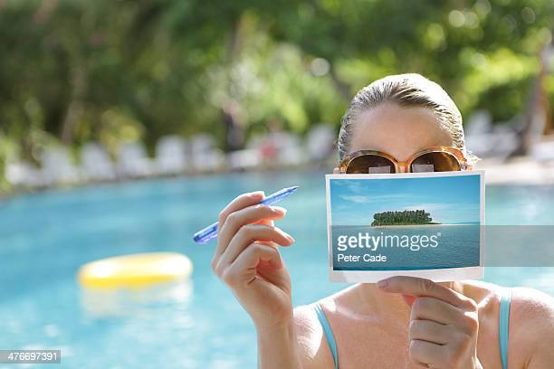 Woman writing postcard by swimming pool