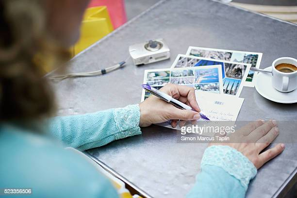 woman writing postcards on table - postcard stock pictures, royalty-free photos & images