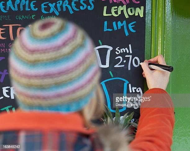 Woman writing price on menu board.