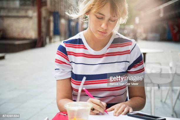 Woman writing, sitting in outdoor cafe, in a urban square.