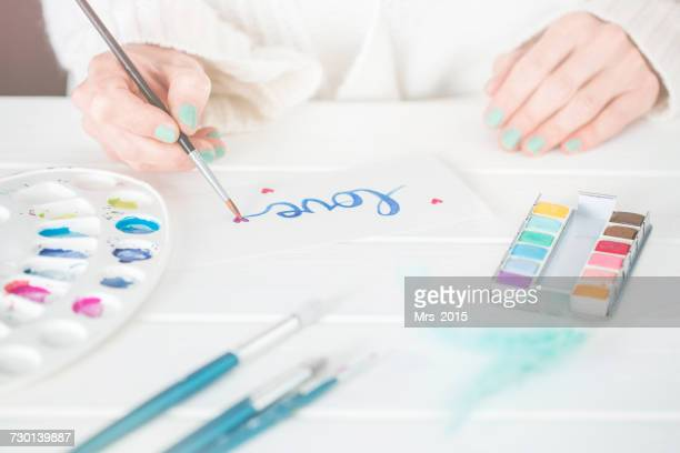 Woman writing the word love in watercolor paint