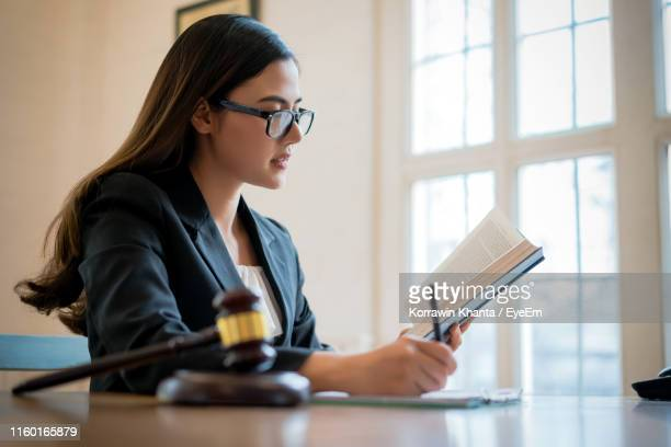 woman writing while reading book on table - 法律関係の職業 ストックフォトと画像
