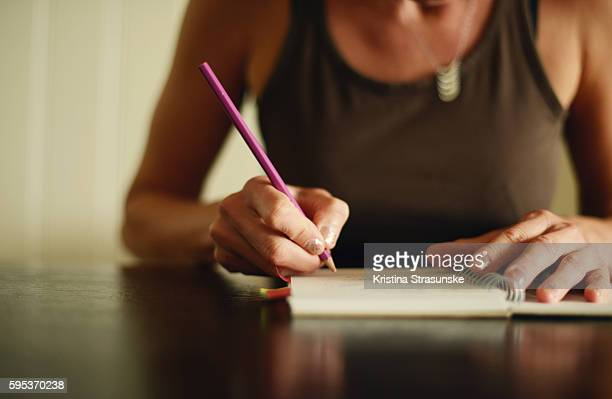 woman writing with a pen in a notebook