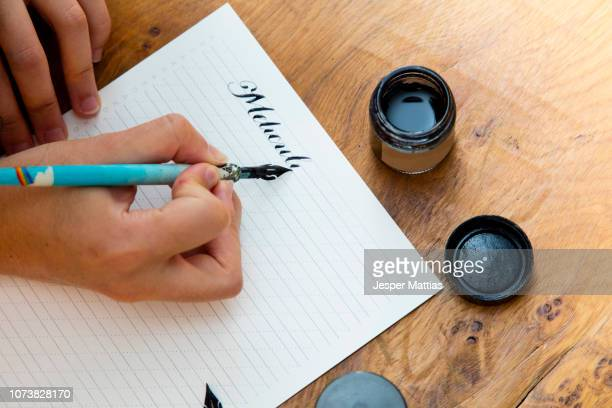woman writing with calligraphy pen - calligraphy stock photos and pictures