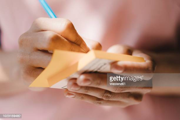 woman writing with pen on adhesive notes - notizbuch stock-fotos und bilder
