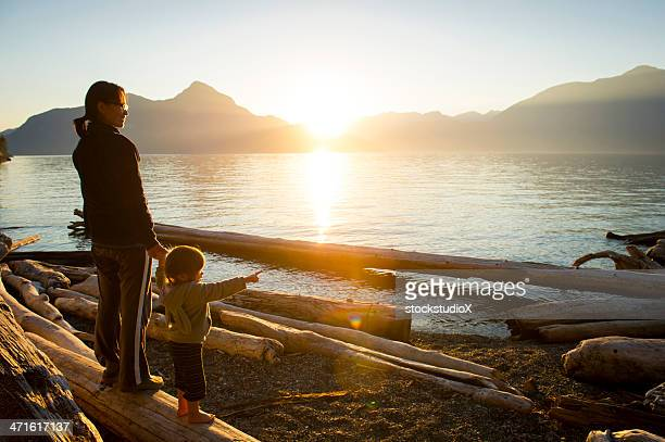 Woman w/small child pointing out to body of water at sunset