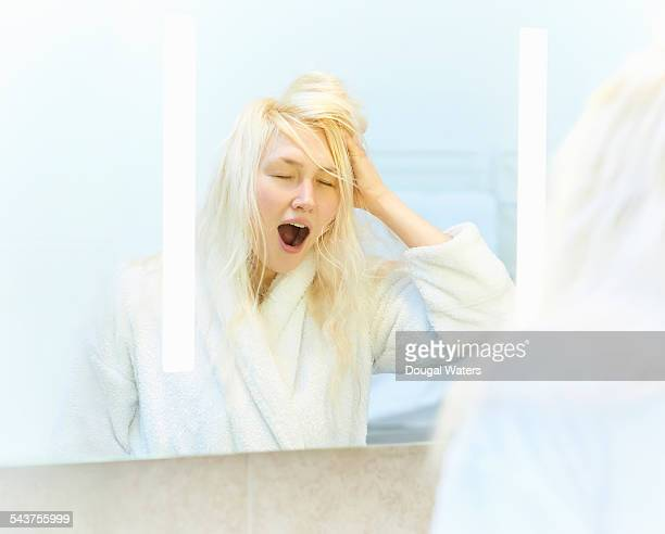 Woman yawning in front of mirror