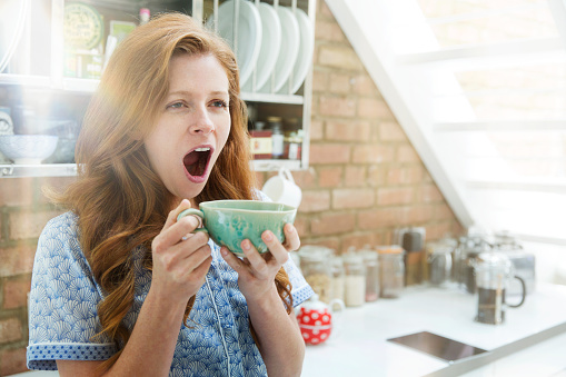 Woman yawning with coffee - gettyimageskorea