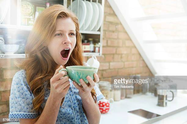 woman yawning with coffee - routine stock-fotos und bilder