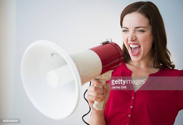 woman yelling through megaphone - megaphone stock pictures, royalty-free photos & images