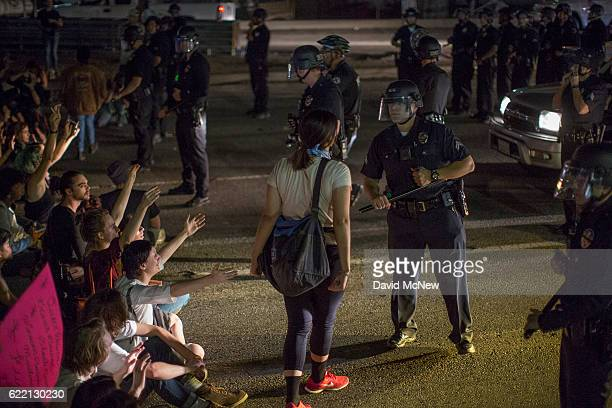A woman yells at a police officer as protesters shut down the 101 freeway in opposition to the upset election of Republican Donald Trump over...