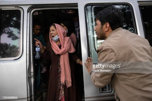 Woman yells for her family to hurry up as displaced Afghans from the northern provinces are evacuated from a makeshift IDP camp in Share-e-Naw park...