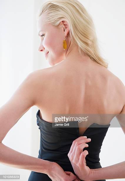 Woman zipping up black dress