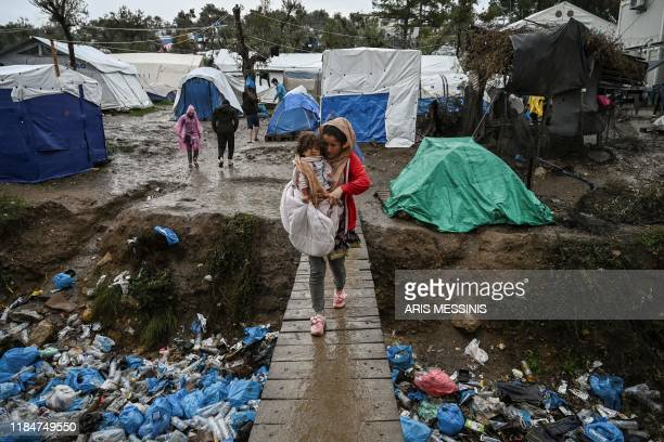 TOPSHOT A womancarries her child as she crosses a wooden bridge in the refugee camp of Moria on the island of Lesbos on November 26 2019 Conditions...