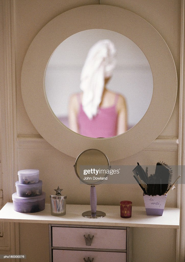 Woman's back being reflected on mirror : Stockfoto