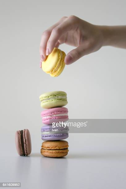 Womans Beautiful Hand Holding A Delicious Colorful Macaroons with Reflection