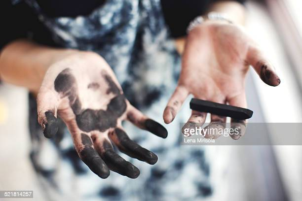Woman's charcoal-stained hands