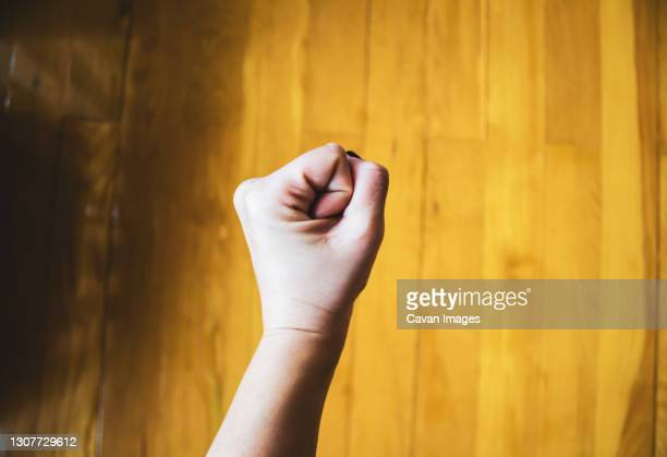 woman's clenched fist against parquet floor - black nail polish stock pictures, royalty-free photos & images