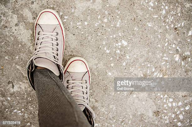 Woman's crossed feet with sneakers on