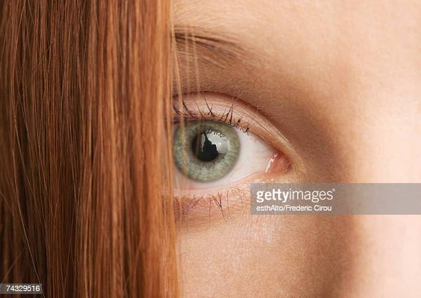 Woman's eye and red hair, close-up