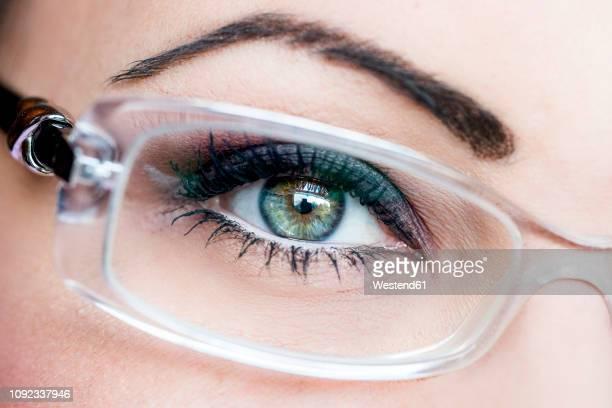 woman's eye, glasses, close-up - brillen en lenzen stockfoto's en -beelden