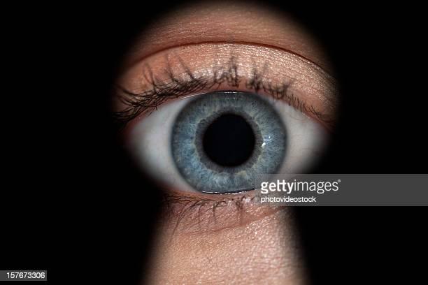 Woman's eye in keyhole