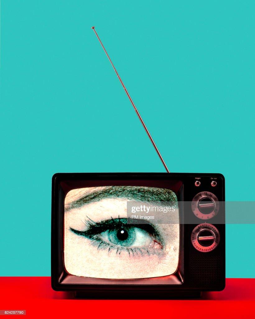 Woman's eye on vintage TV : Stock Photo
