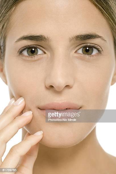 woman's face, fingers on cheek, close-up - occhi nocciola foto e immagini stock