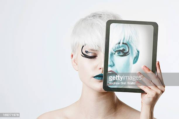 Woman's face half hidden by computer tablet photo