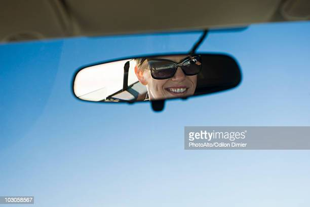 Woman's face reflected in rearview mirror