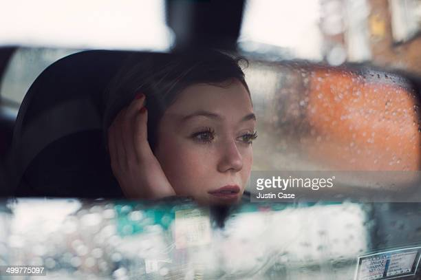 woman's face seen in the rear mirror of a car
