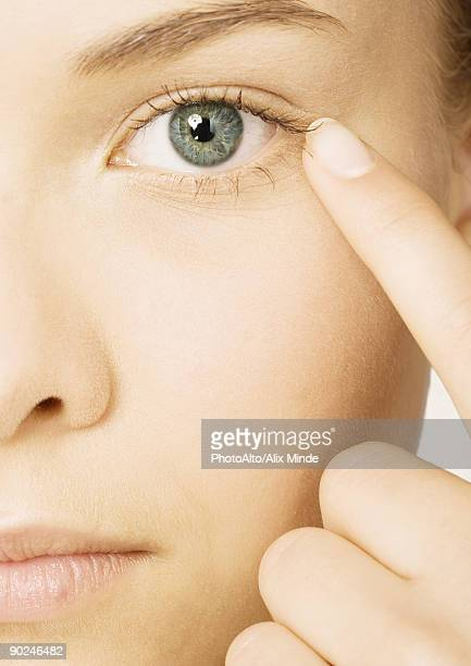 Woman's face with finger next to eye, extreme close-up