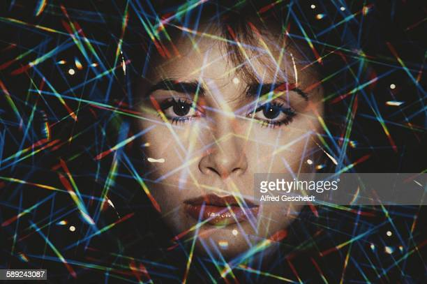 A woman's face with rainbowcoloured flecks of light superimposed over it 1978