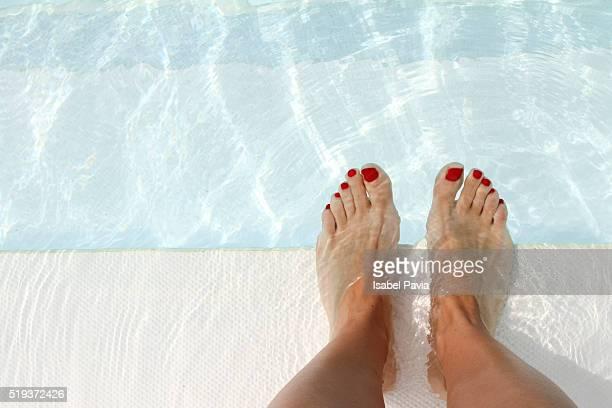 Woman's feet at edge of swimming pool