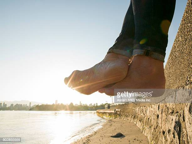 Woman's feet dangle from stone wall, sea and city