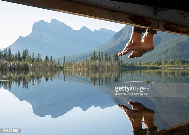 Woman's feet dangle from wooden dock, above lake