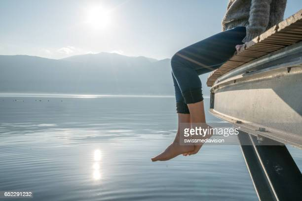 woman's feet dangle from wooden wharf, above lake - white women feet stock pictures, royalty-free photos & images